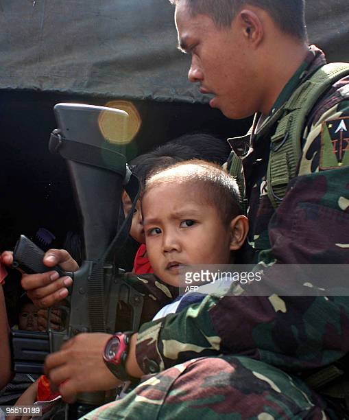 A soldier carries a child on board their vehicle during a forced evacuation of residents living at the foot of the Mayon volcano in Bonga near the...