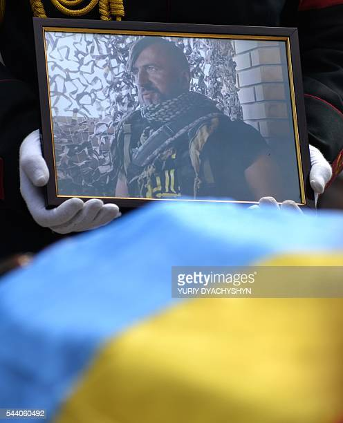A soldier carries a portrait of Wassyl Slipak as people take part in his funeral ceremony in the western Ukrainian city of Lviv on July 1 2016 A...