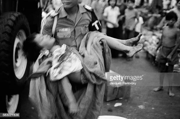 A soldier carries a wounded child after the first rocket attacks announcing the North Vietnamese entry into Saigon Fourteen died and over forty...