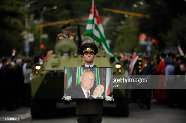A soldier carries the portrait of Sergei Bagapsh the head of Georgia's rebel Abkhazia region in front of the armored vehicle pulling a gun carriage...