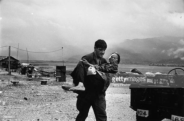 A US soldier carrying a wounded refugee to safety during the war in Vietnam