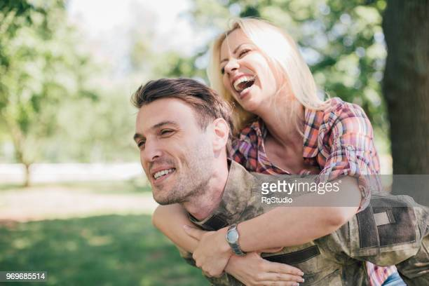 soldier carrying his joyful wife - military spouse stock pictures, royalty-free photos & images