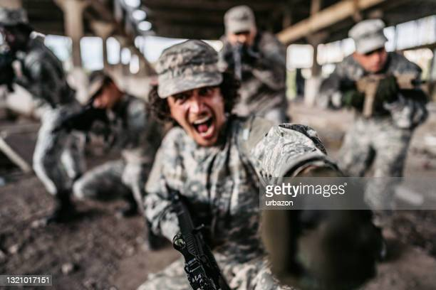 soldier charging in battle with his squad - military attack stock pictures, royalty-free photos & images