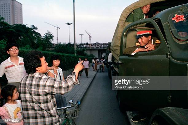 A soldier chats with onlookers while prodemocracy demonstrators prevent his convoy of trucks filled with soldiers from entering Tiananmen Square just...