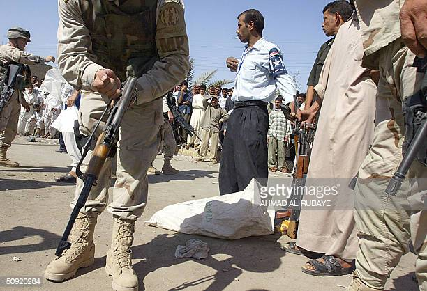 US soldier checks a rifle bought off an Iraqi civilian as people gather to watch US troops and Iraqi police buying up civilian owned weapons in the...