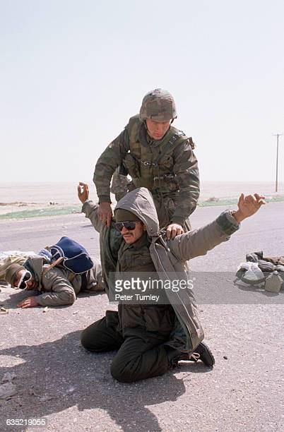 A US soldier checks an Iraqi soldier taken as a prisoner of war after the liberation of Kuwait in the Gulf War