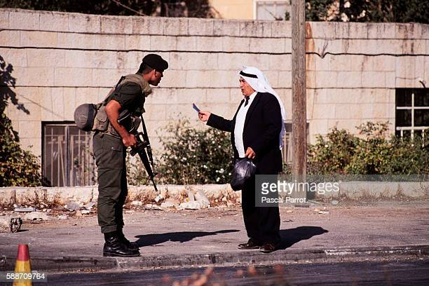 Soldier Checks Identity Papers of a Palestinian Man in Jerusalem