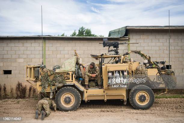 Soldier checks the tyres of a Jackal armoured vehicle following a patrol during a military exercise on Salisbury Plains on July 23, 2020 near...
