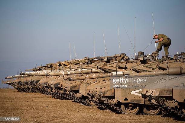 Soldier cleans his shoos on top of a tank as Israeli troops take part in a military exercise on August 28, 2013 near the border of Syria, in the...