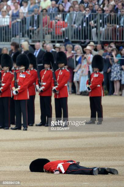 A soldier collapses on Horse Guards Parade ahead of the Queen's Birthday Parade 'Trooping the Colour' in London on June 11 2016 Trooping The Colour...