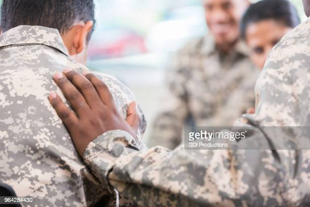 soldier comforts friend during support group meeting - soldier praying stock photos and pictures