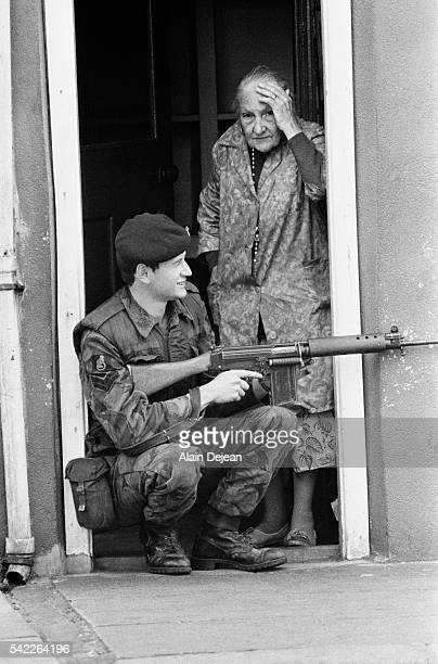 A soldier crouches in the doorway of the home of an elderly woman after conflicts broke out in Belfast Northern Ireland in reaction to the British...