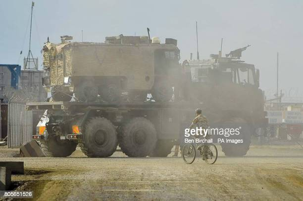 A soldier cycles infront of a huge Improved Medium Mobility Load Carrier truck with a Vector troop carrying vehicle on the back that it is delivering...