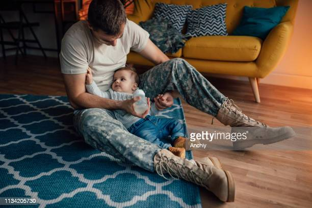 Soldier dad bottle feeding his little boy