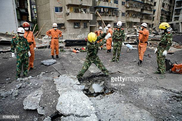 A soldier digs a hole as rescue workers standby on the rooftop of a collapsed building in the completely destroyed city of Beichuan Sichuan China A...