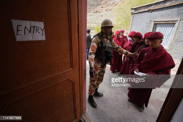 A soldier directs a Buddhist monk into a polling station near the Hemis Monastery about 45km from Leh in India's Ladakh region on May 6 2019 India...