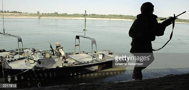 S soldier disembarks his vessel after undertaking a patrol of the waterways around former Iraqi leader Saddam Hussein's home town July 28 2003 in...