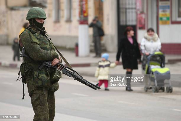 Soldier displaying no identifying insignia carries a loaded, heavy machine gun as people walk past in the city center on March 1, 2014 in Simferopol,...