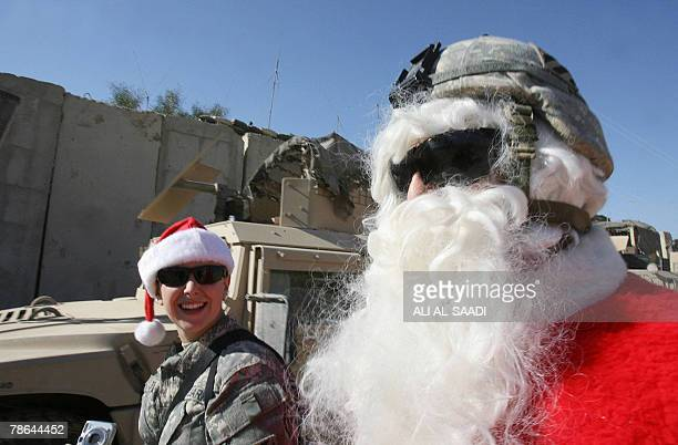 Soldier dressed as Santa Claus laughs with a female soldier at the Hammer base in southern Baghdad on Christmas eve, 24 December 2007. Christians...