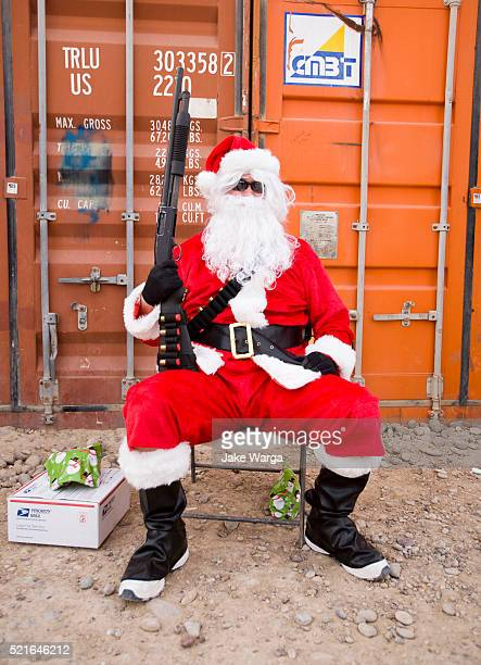 u.s. soldier dressed for christmas as santa guarding storage containers with a mossberg shotgun. - jake warga stock pictures, royalty-free photos & images