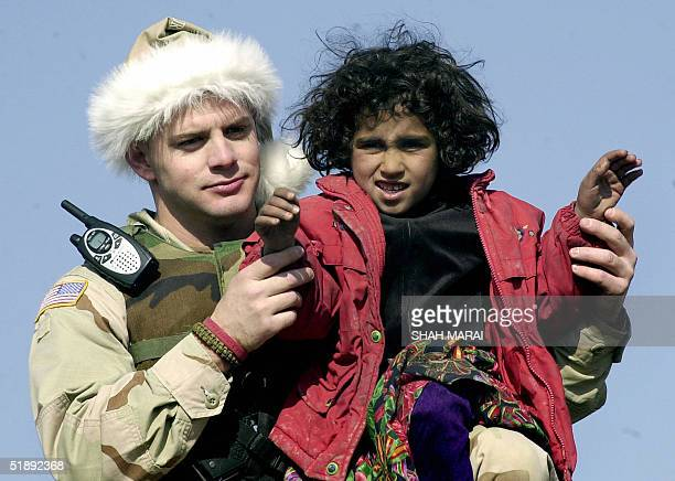 S soldier dressed in a Santa Claus hat plays with a small Afghan girl during a humanitarian operation dubbed 'Operation Goodwill' in the village of...