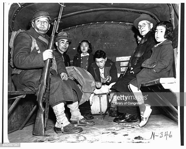 A soldier escorts several Japanese American children and a pastor in the back of a truck during their evacuation from Bainbridge Island to a...