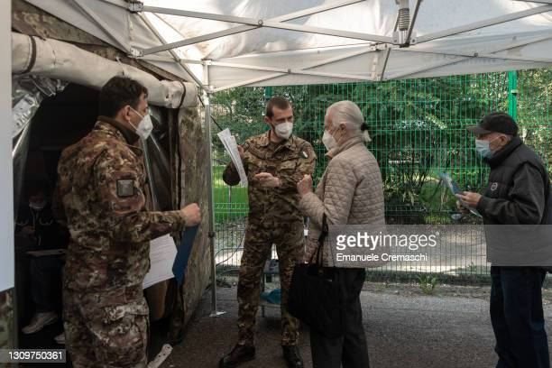 Soldier explains people over 80 years old how to fill some documents as they arrive at Milan's Military Hospital to receive the first dose of the...
