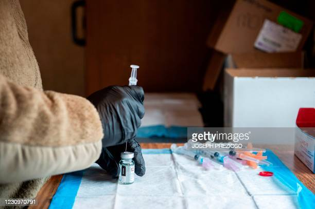Soldier fills syringes with the Moderna Covid-19 vaccine inside a trailer at a vaccination center in Londonderry, New Hampshire on February 4, 2021....