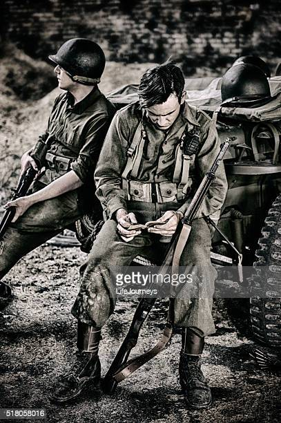 wwii soldier finding comfort reading his scriptures - boots rifle helmet stock pictures, royalty-free photos & images
