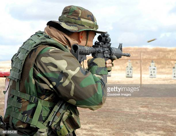 A soldier fires rounds down range at an M-4 qualification shoot.