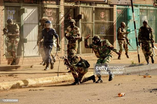TOPSHOT A soldier fires shots towards demonstrators on August 1 2018 in Harare as protests erupted over alleged fraud in the country's election...