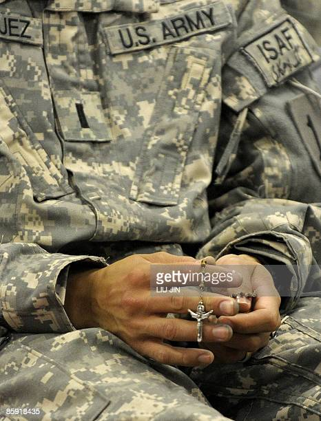 Soldier from 1st Infantry Division holds a rosary during an Easter Sunday Mass at the Raider Chapel in ISAF's Camp Bostick in Naray, in the eastern...