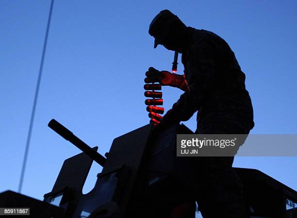 A US soldier from 1st Infantry Division prepares the rounds of bullets on a humvee before leaving the ISAF's Camp Bostick for a mission to search for...