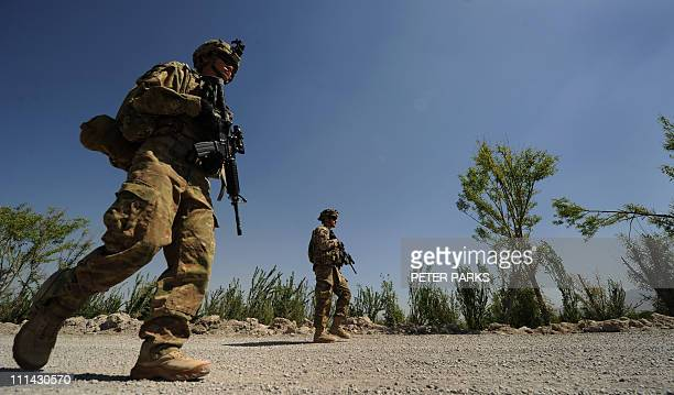 A US soldier from 1st Regiment 320 Field Artillary 101st Airbourne walks to the opening ceremony for a newly completed mosque in the village of Tarok...