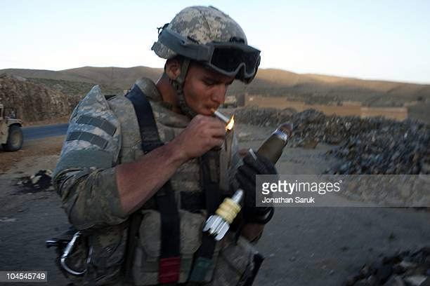 US soldier from 3rd Brigade 10th Mountain Division lights a cigarette after firing mortars at an enemy position after when convoy came under attack...