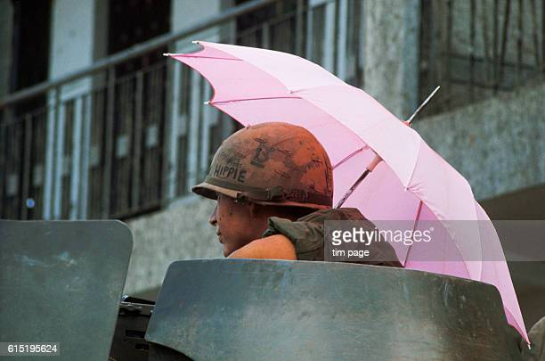 A US soldier from 8ieme Regiment riding atop a 9th Division armored personnsl carrier shelters beneath a pink umbrella at Saigon during the miniTet...