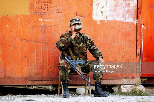 A soldier from A company drinks and eats as he sits at base camp in the village of Tamaracheni South Ossetia Georgia on September 14 2004 The...