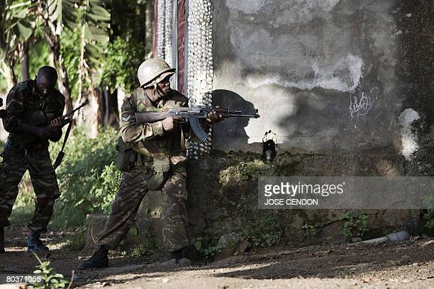 A soldier from a unit of Comoran and Tanzanian African Union troops aims at the positions of supporters of renegade Anjouan leader Mohamed Bacar in...