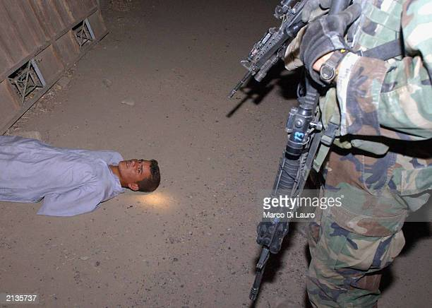 S soldier from Alfa Company 1/18 Infantry 4th Infantry Division out of Fort Carson Colorado guards a prisoner captured during a raid to arrest senior...