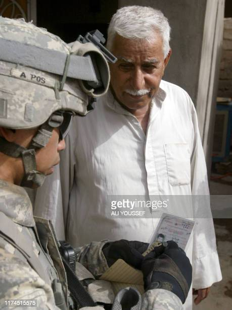 A US soldier from Fox company 4th squadron 2nd Stryker Cavalry Regiment checks the identity of an Iraqi man in western Baquba northeast of Baghdad on...