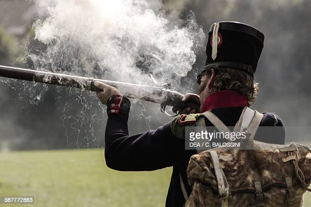Soldier from Napoleon's line infantry firing a muzzle-loading flintlock rifle. Napoleonic wars, 19th century. Historical reenactment.
