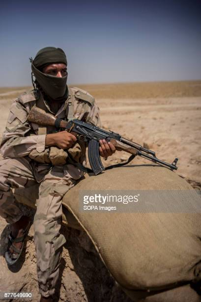 A soldier from Quwat Al Nukhba takes fire towards a Islamic State position in a village a kilometre away from their bunker