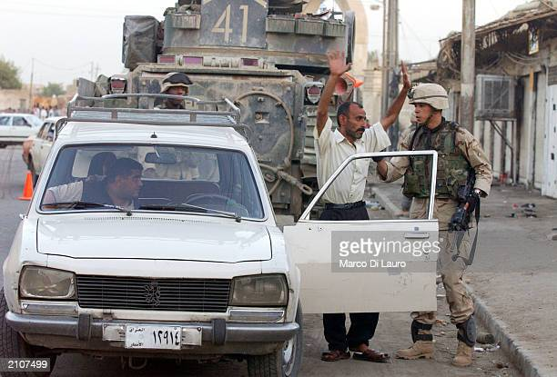 Soldier from the 1st Armored Division check an Iraqi driver during a raid looking for possible weapons stocks June 23 2003 in the AlshekMaruf...
