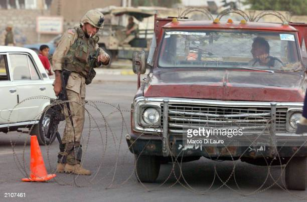 S Soldier from the 1st Armored Division directs a car at a street check point during a raid into a cemetery and mosque looking for possible weapons...