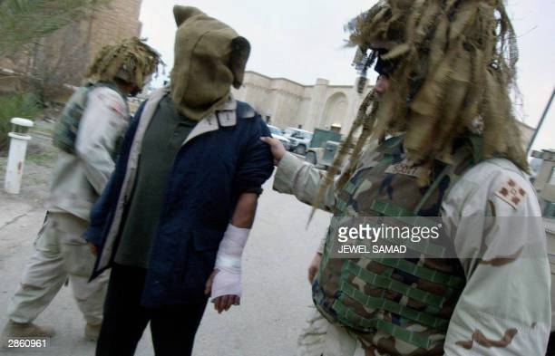 Soldier from the 1st Battalion, 22nd Regiment of the 4th Infantry Division pulls an Iraqi detainee to a makeshift prison after taking him for medical...