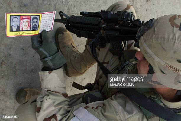 S soldier from the 1st Battalion 24th Infantry Regiment collects a pamphlet Iraq's most wanted man Jordanian Abu Musab alZarqawi during a patrol in...