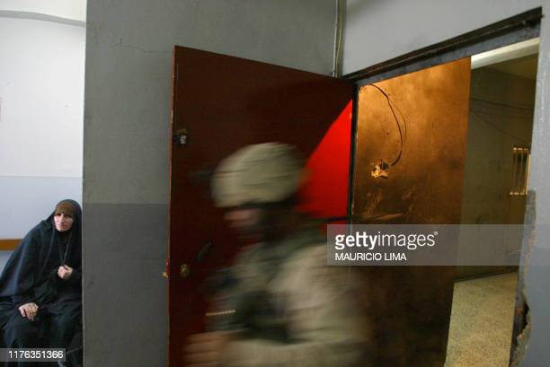 A US soldier from the 1st Battalion 24th Infantry Regiment enters into a dentist clinic as an Iraqi woman waits to be attended in the Muslim Sunni...