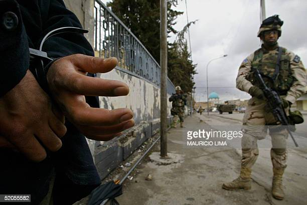 Soldier from the 1st Battalion, 24th Infantry Regiment guards an Iraqi detainee man during a patrol in a comercial area, in the northern Iraqi city...