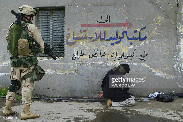 Soldier from the 1st Battalion, 24th Infantry Regiment guards an Iraqi detainee during a patrol in a commercial area, in the northern Iraqi city of...