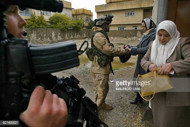 US soldier from the 1st Battalion 24th Infantry Regiment inspects a bag of Iraqi women during a patrol looking for car bombs and insurgents...